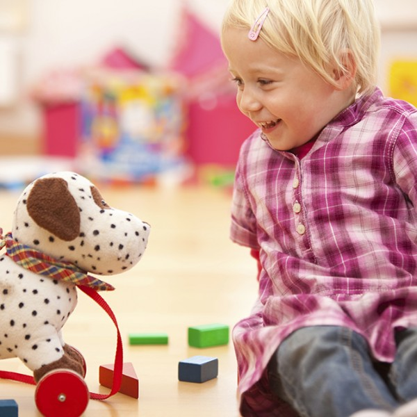 Girl Playing with Toy Dog