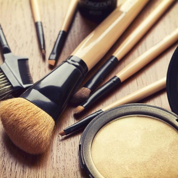 Set of makeup brushes and gold bronzer highlighter powder